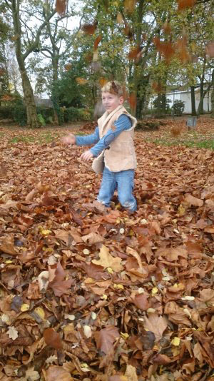 a boy in a lambskin-vest is playing in autumn leaves